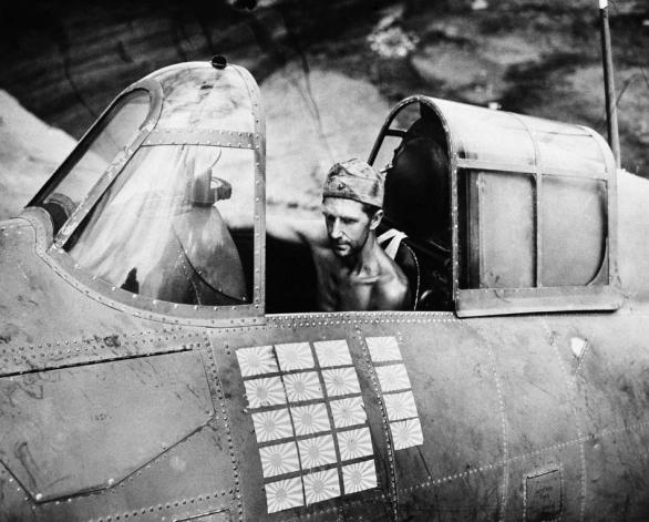 March 22, 1943: Technical Sgt. R.W. Greenwood, a Marine, sits in the cockpit of a Grumman Wildcat fighter plane, based at Henderson Field, Guadalcanal, that is credited with shooting down 19 Japanese aircraft, as illustrated by the number of Japanese flags on his plane. Several different pilots have flown the ship during successful missions, but Sgt. Greenwood has remained plane captain. (AP Photo)
